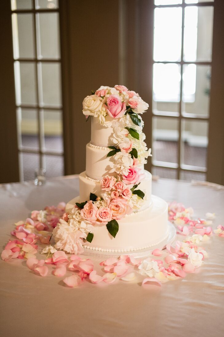 Kylie and Travis enjoyed a four-tier white buttercream cake with cascading roses and hydrangeas to match the romantic wedding theme.