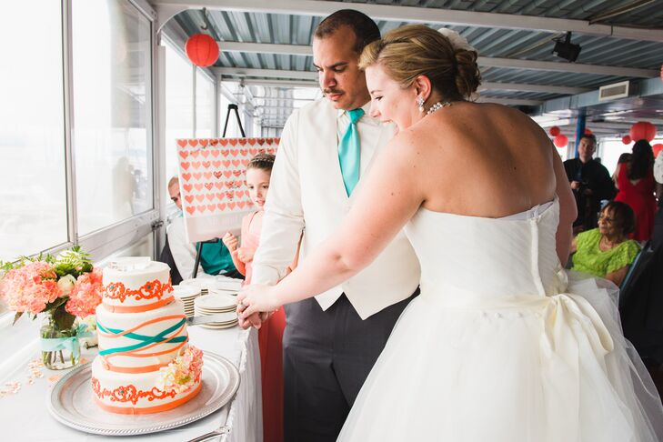 The couple cuts into their three tier white cake with coral and turquoise fondant accents.