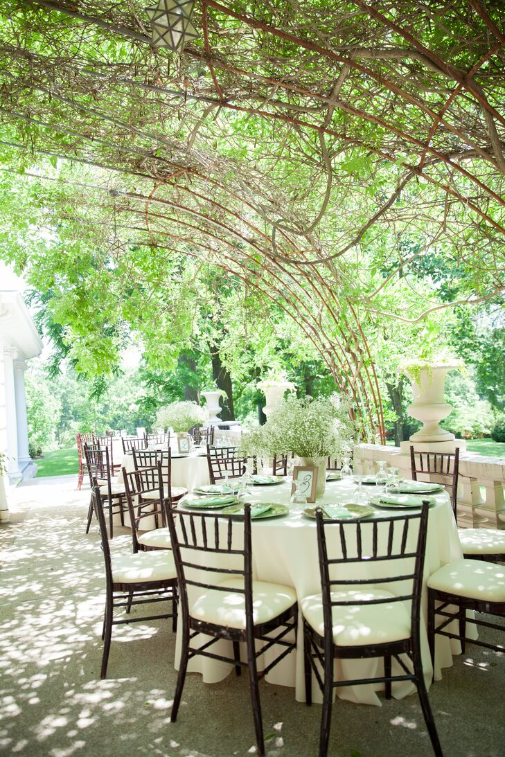 The reception took place outside at Liriodendron Mansion in Baltimore, Maryland, where guests sat around dining tables positioned under a canopy of trees. The baby's breath centerpieces allowed the setup to blend easily with the natural setting.