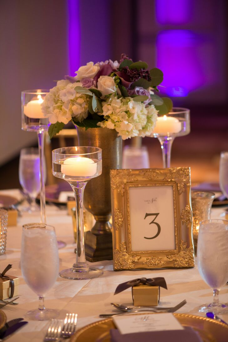 Black-and-white table numbers in detailed gold frames continued the glam motif. Floating tea candles surrounding low lavender and white floral centerpieces toned down the room.