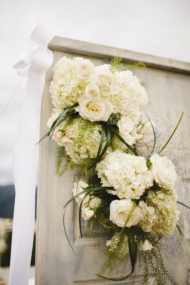 Clusters of white roses and hydrangeas decorated the ceremony site.