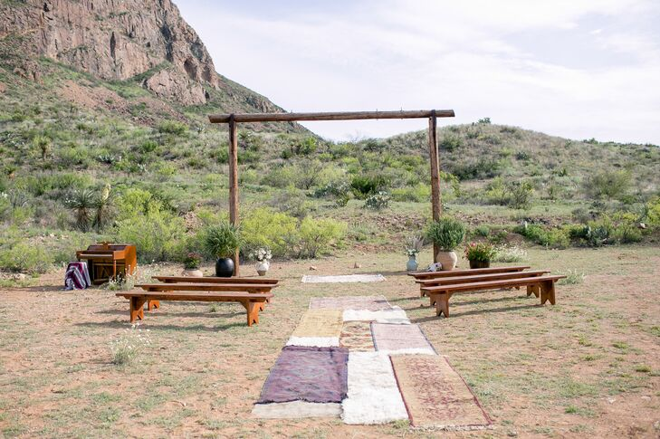 Valerie and Taylor added wooden benches around their ceremony location for half of their guests and let the others gather around for an intimate atmosphere. They surrounded the rustic wooden wedding arch with urns filled with fresh flowers and brought in vintage rugs to create the aisle.