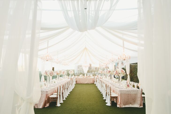 In lieu of the traditional tent, Jocelyne and Nick covered their elegant blush reception tables with an ethereal structure of draped white fabric. The open-air tent heightened the evening's romantic feel and allowed guests to profit from the rooftop's striking views and the city's twinkling lights.