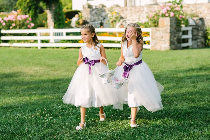 The flower girls' attire perfectly captured Kimberly and her bridesmaid look. The duo walked down the aisle in flowing full tulle dresses adorned with brilliant purple bows. Their hair was perfectly coiffed into curled half-up styles, which mirrored Kimberly's.