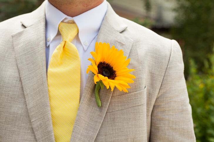 The groom wore a tan suit with a yellow tie and sunflower boutonniere to match the casual feel of the wedding.