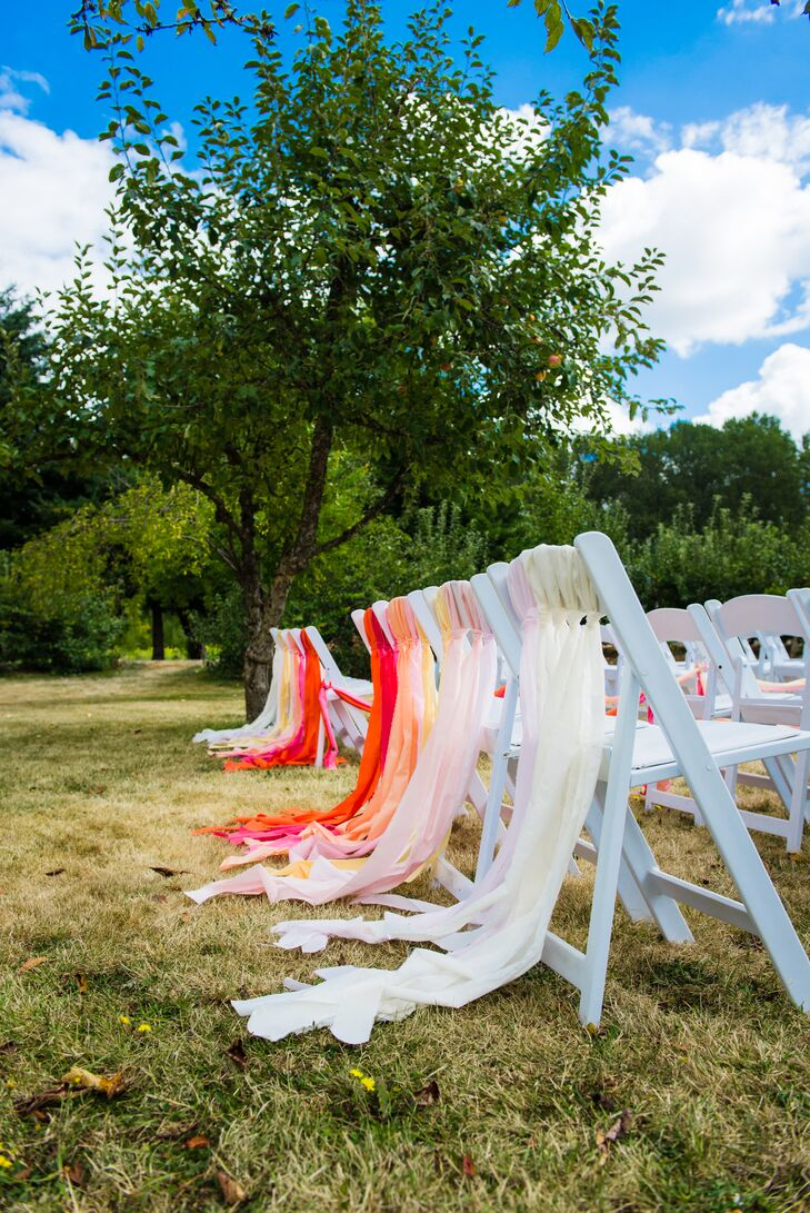 The back row of ceremony chairs was decorated with ombre pink orange and white streamers to add a whimsical touch to the celebration.