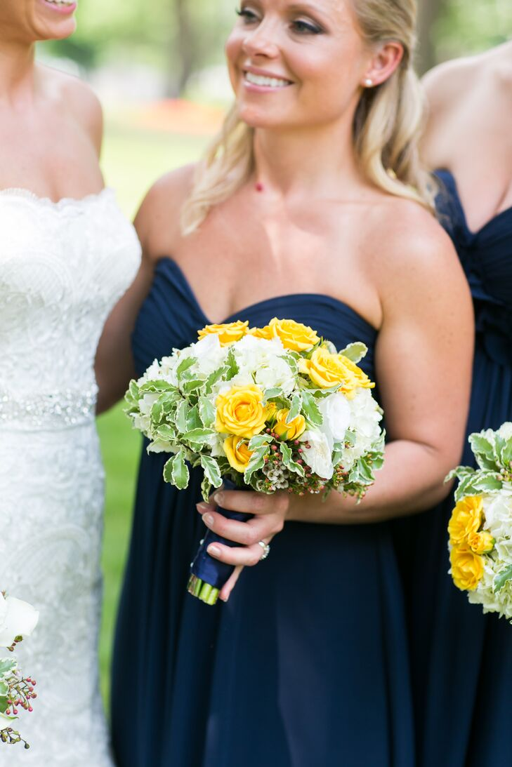 With navy, white and gold used throughout their decor, the hues had to be included in the bridesmaid looks. Each woman carried this lush display of yellow roses, white lisianthus and greenery wrapped in navy ribbon. Small red hypericum berries accented the side for an unexpected, added color.