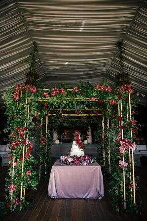 Cake Table Surrounded by Wood Arches and Red and Pink Blooms