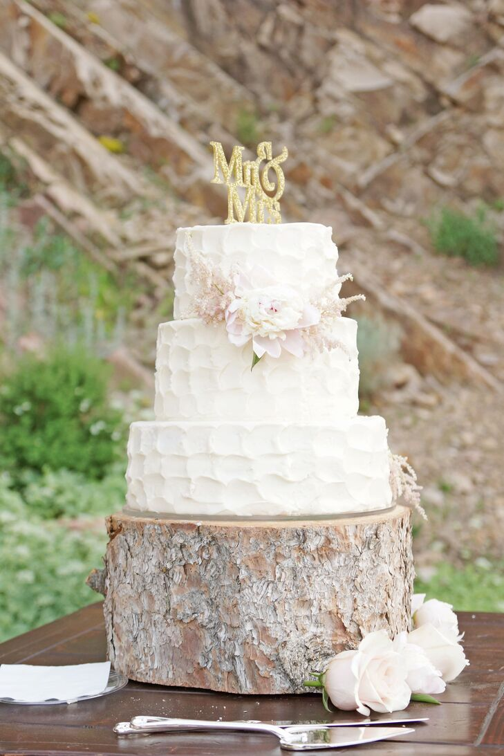 "Heritage Cakes created a three-tier confection covered in textured white buttercream, accented by a pink peony surrounded by astilbes and topped with a gold ""Mr. & Mrs."" A wooden slab cake stand tied in the display with the natural decor."
