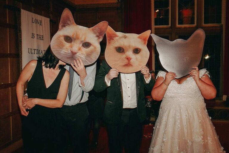 Wedding guests holding cat signs in front of their faces