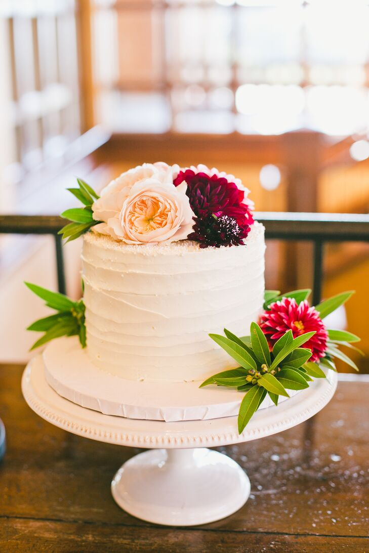 For dessert, Nicki and Jordan passed on a colossal confection and had Moustache Bakery whip up a small one-tier wedding cake for the traditional cake cutting. The pint-sized sweet was decorated with textured buttercream and dahlias and roses in peach and burgundy hues.