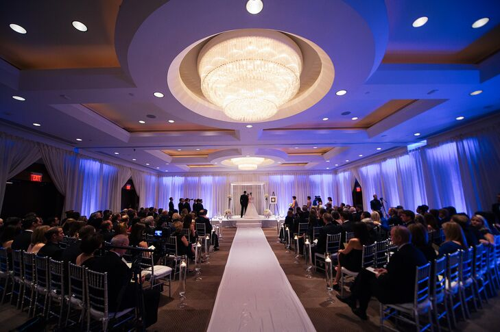 The couple was married in a Jewish ceremony under a crisp white chuppah. To add a bit of glamour to their ballroom ceremony, Joan and Jon had all of the walls draped with white fabric and then illuminated with blue up-lighting. Huge crystal chandeliers hung above the white ceremony aisle that was also lined with floating candles in glass vases.
