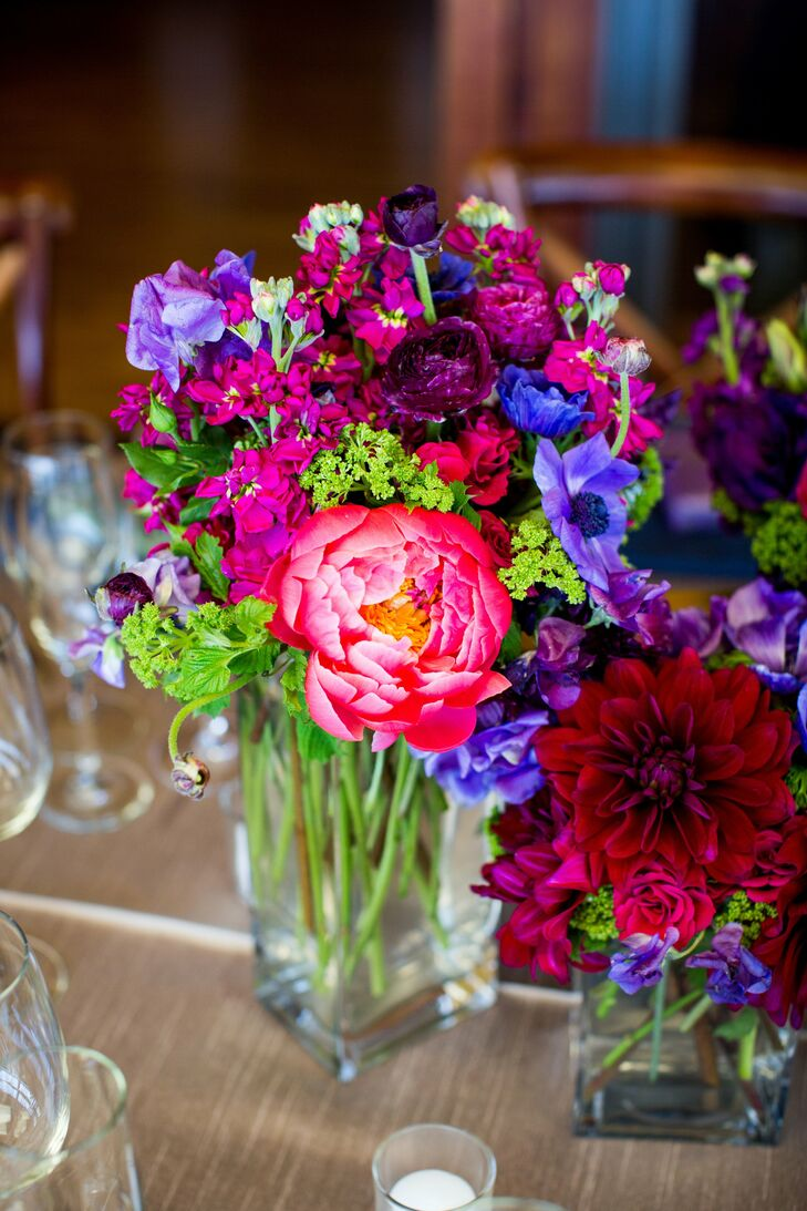 Large colorful centerpieces filled with ranunculuses, anemones, tulips, garden roses and stock decorated some of the tables.