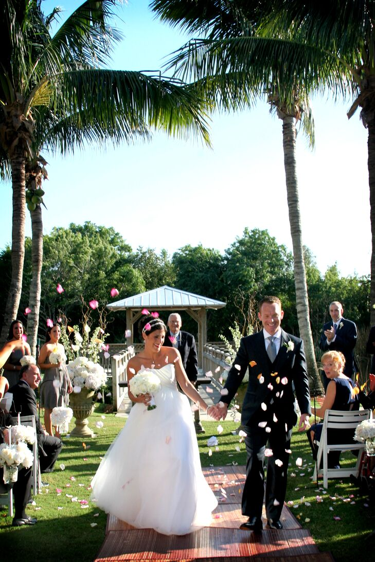 The couple left their ceremony under a shower of pink, white and orange flower petals thrown by their guests.