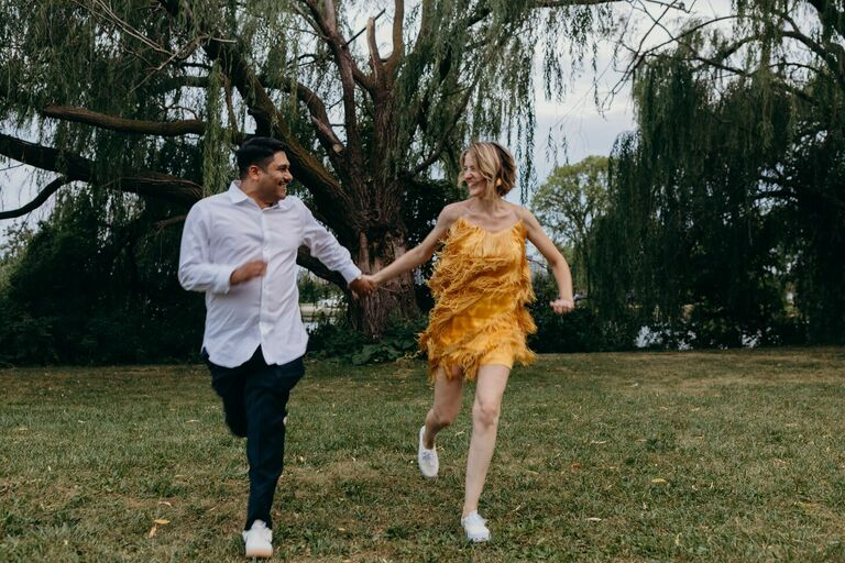 Couple holding hands and running through field