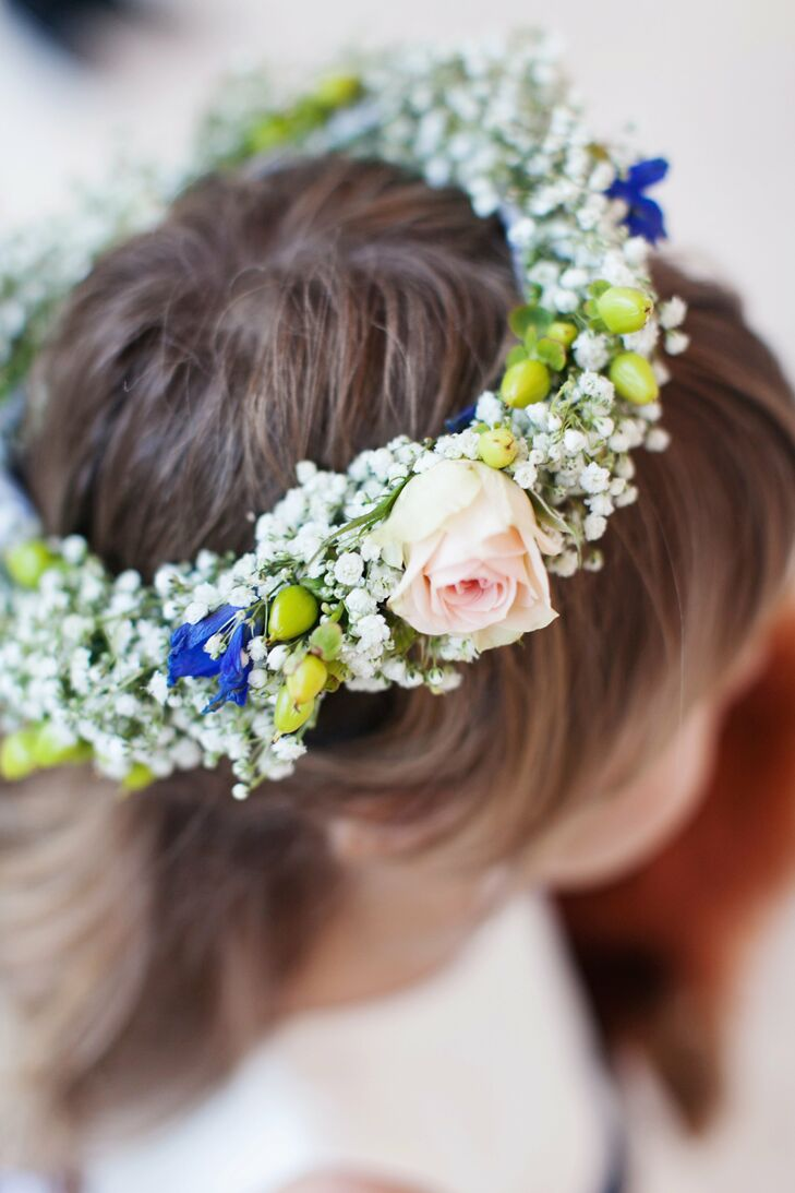 The glower girl matched her bright floral pomander with a flower crown made from baby's breath, hypernicum berries, cornflowers and roses in white, blue, green and blush.