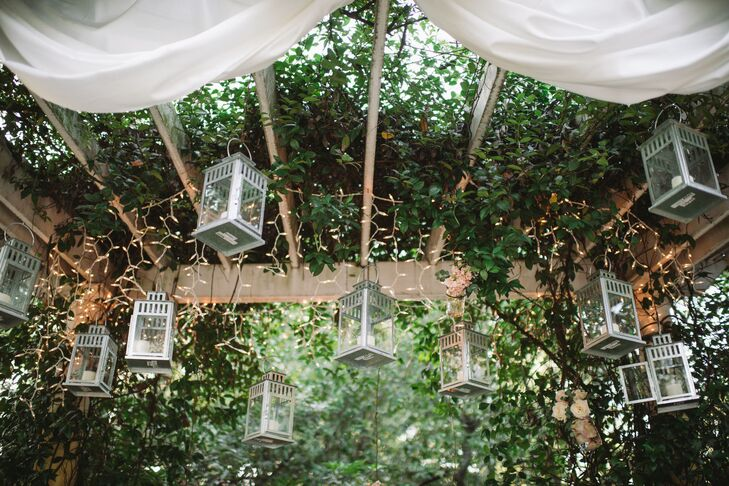 Mason jars filled with flowers and candles were placed in lanterns and hung from the couple's ceremony arbor.