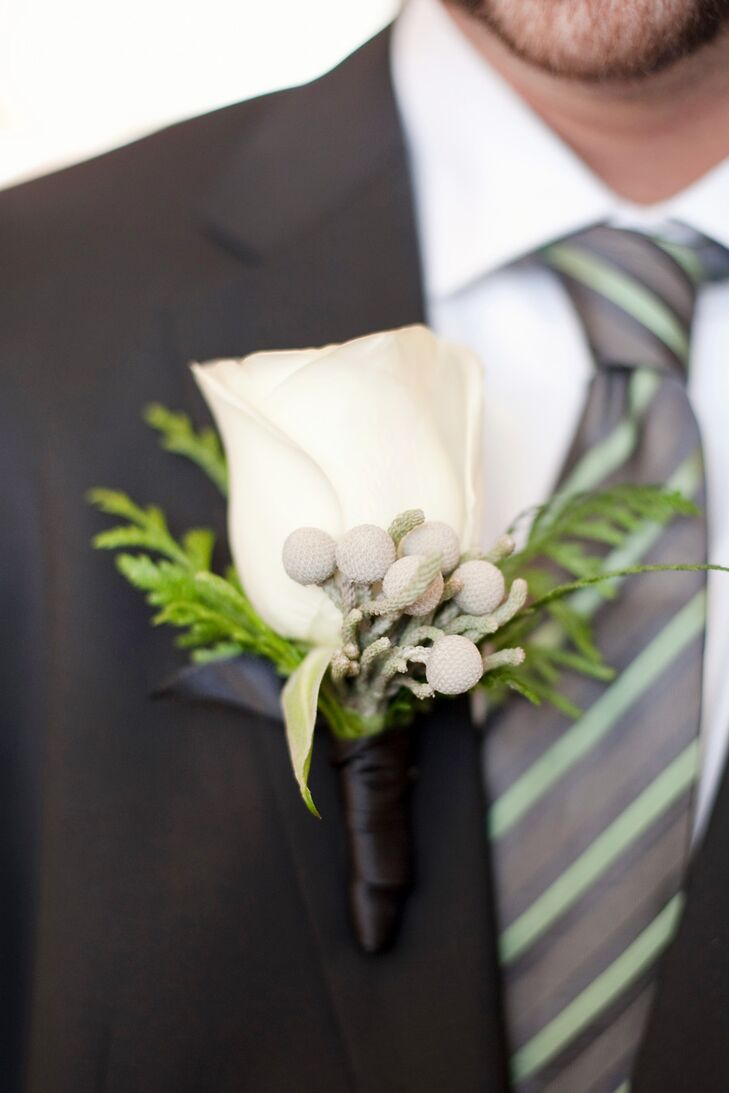 The groom wore a white rose accented with pine and silver brunia balls for his boutonniere.