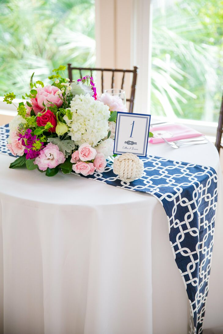 Navy-patterned table runners were draped over white table linens and topped with a bright floral arrangement of Callie's favorite flowers, including hydrangeas, peonies and dusty miller. Balls of white rope were used to display table numbers printed on navy and white stationery with a sailor's knot.