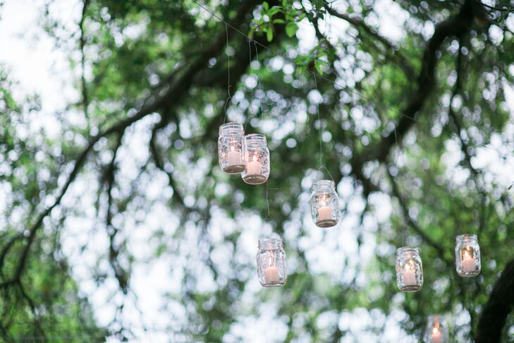 As yards of string lighting were hung over the dance floor, Megan and Santi added a rustic touch to their lighting design with a few dozen mason jars. Each was strung from a grand oak tree as white candles within the jars added a welcome glow to their candy bar and outdoor seating areas. A line of hanging mason jars also led the way to their rented reception.