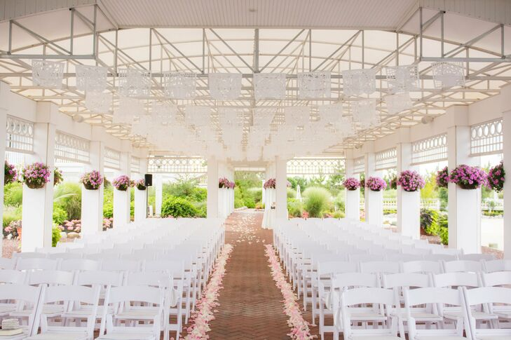 The Boathouse Chapel was the perfect seaside spot for the couple's ceremony. They decorated the open air space with strings of white flags, pink rose petals along the aisles and hanging baskets of pink blooms.