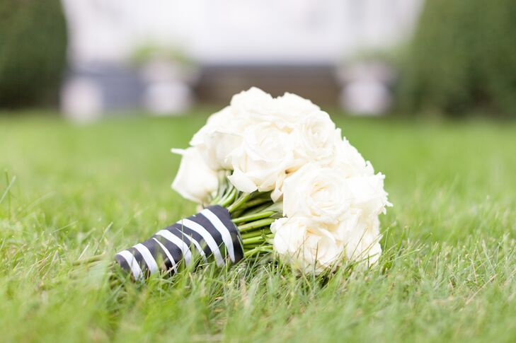 Anna held an elegant, round bouquet filled with ivory roses. The roses were tied together around the stems by a black-and-white-striped wrap.