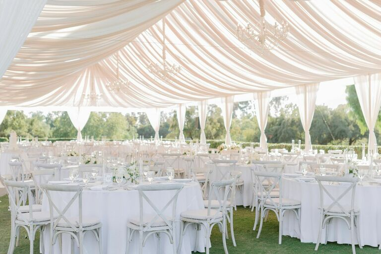 Tented wedding reception with draping and white decor