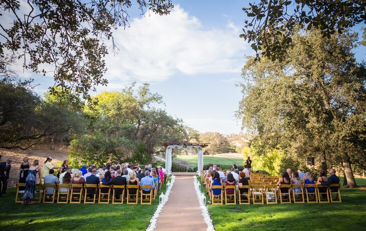 The ceremony took place on the lawn outside at Catta Verdera Country Club in Lincoln, California. The aisle was lined with white petals and lanterns, which led to the wedding arch that was draped in strings of crystals and white linens.