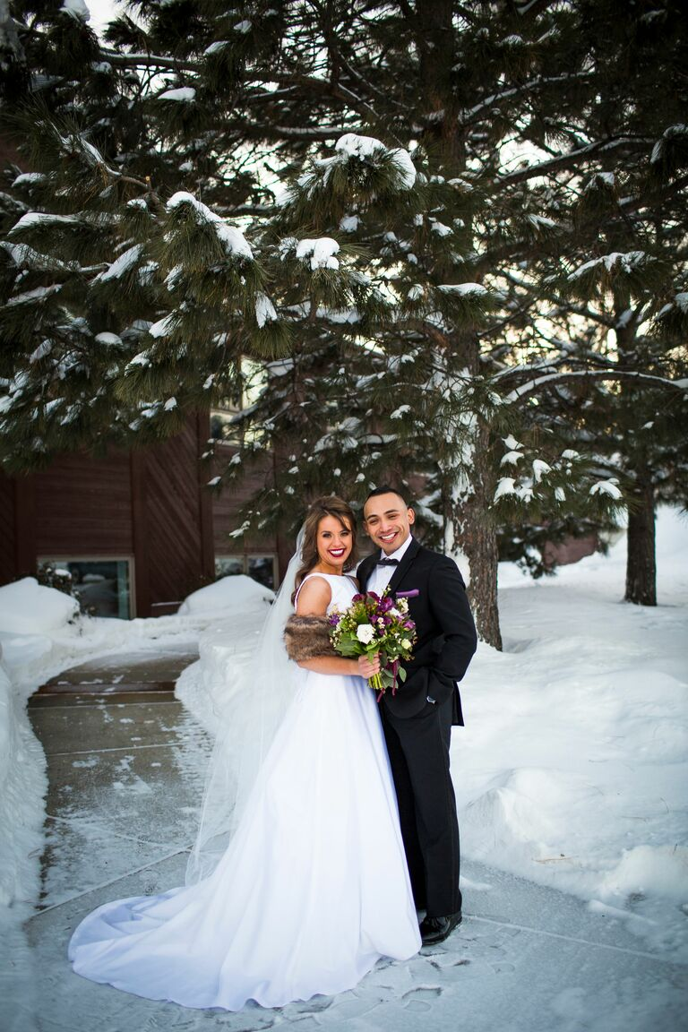 bride and groom posing in the snow