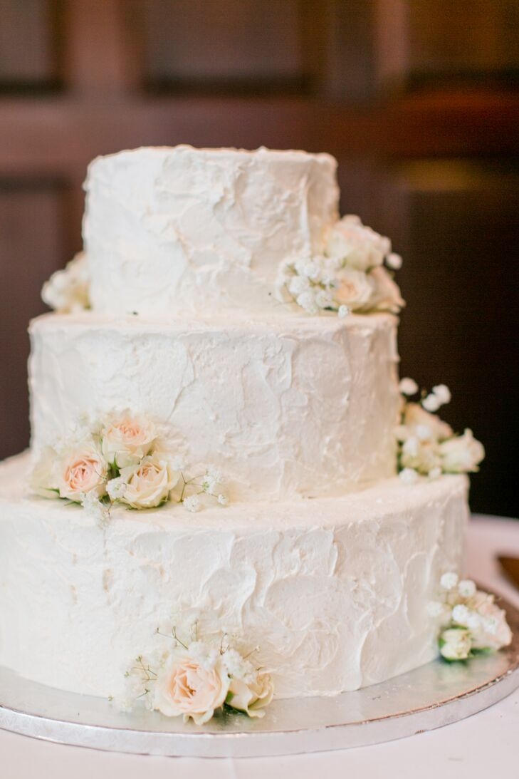 "Wanting a classic-looking cake, Gladys had three tiers with multiple flavors, including red velvet, carrot cake, chocolate and marble iced with plain white buttercream frosting. ""Simple flowers provided by our florist adorned the cake, and we had no other topper,"" Gladys says."