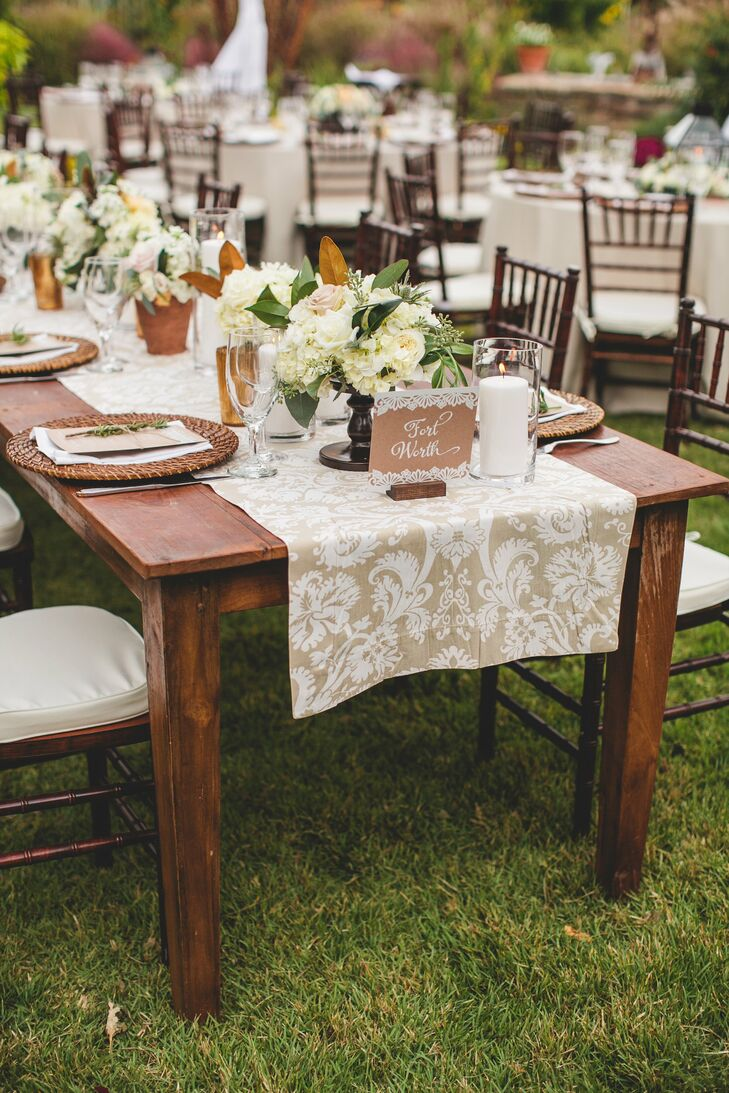 Two long head tables were covered in tan and white damask table runners with low centerpieces and white pillar candles.