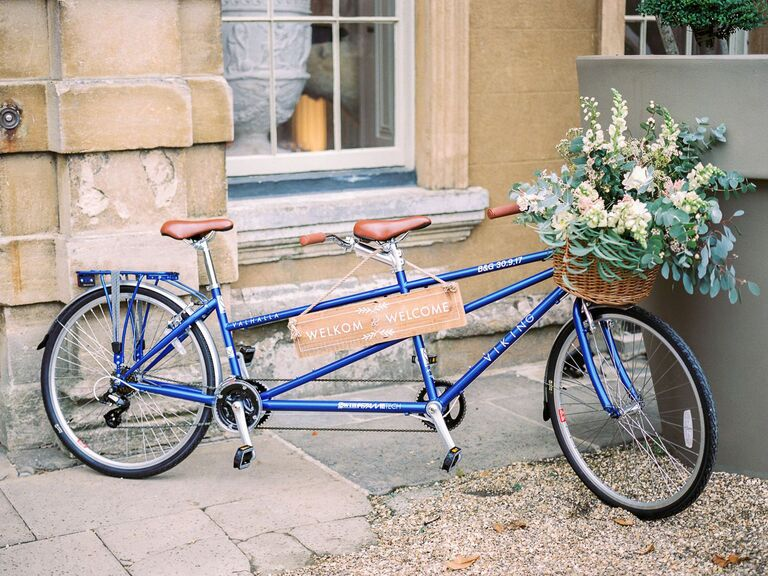 rustic wood wedding sign and blue tandem bicycle and flowers