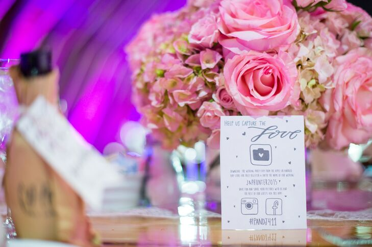 Lush arrangements of pink roses were placed at every table, adding a romantic touch to the centerpiece decor. A small card at each table let guests know the couple's unique wedding hashtag so they could upload photos to Instagram and Facebook.