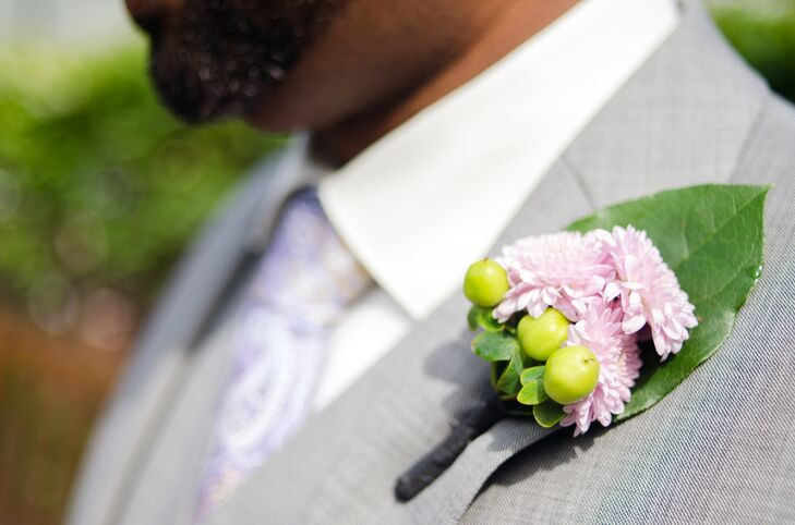 Michael wore a pink chrysanthemum and green hypericum boutonniere with his gray suit on his wedding day. He also wore a purple paisley tie.