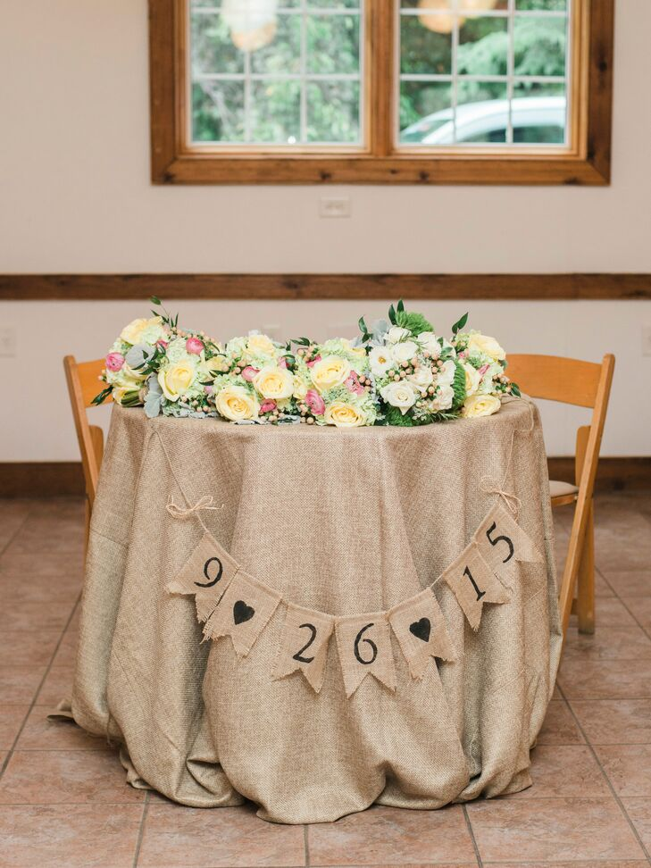 Decorated with the bridal bouquets, Beth and Aaron's sweetheart table was lined with burlap with a flag displaying the couple's wedding date.
