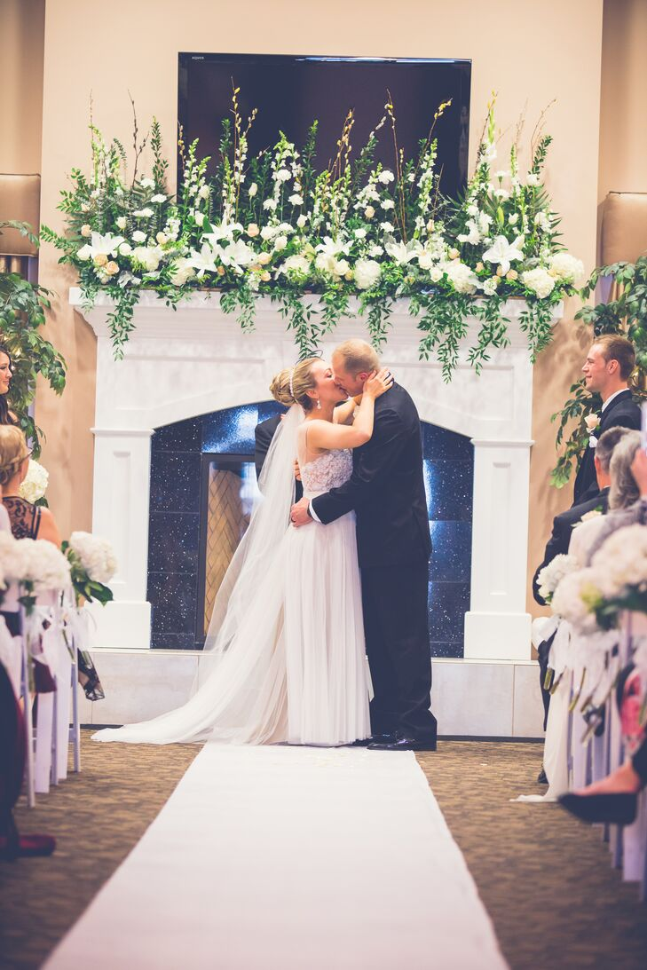 The couple shared their first kiss as a married couple during the indoor ceremony at Grand Oaks Event & Business Center in Grove City, Ohio. They stood in front of the white fireplace, which was decorated with an assortment of ivory hydrangeas, roses and lilies accented with greenery.