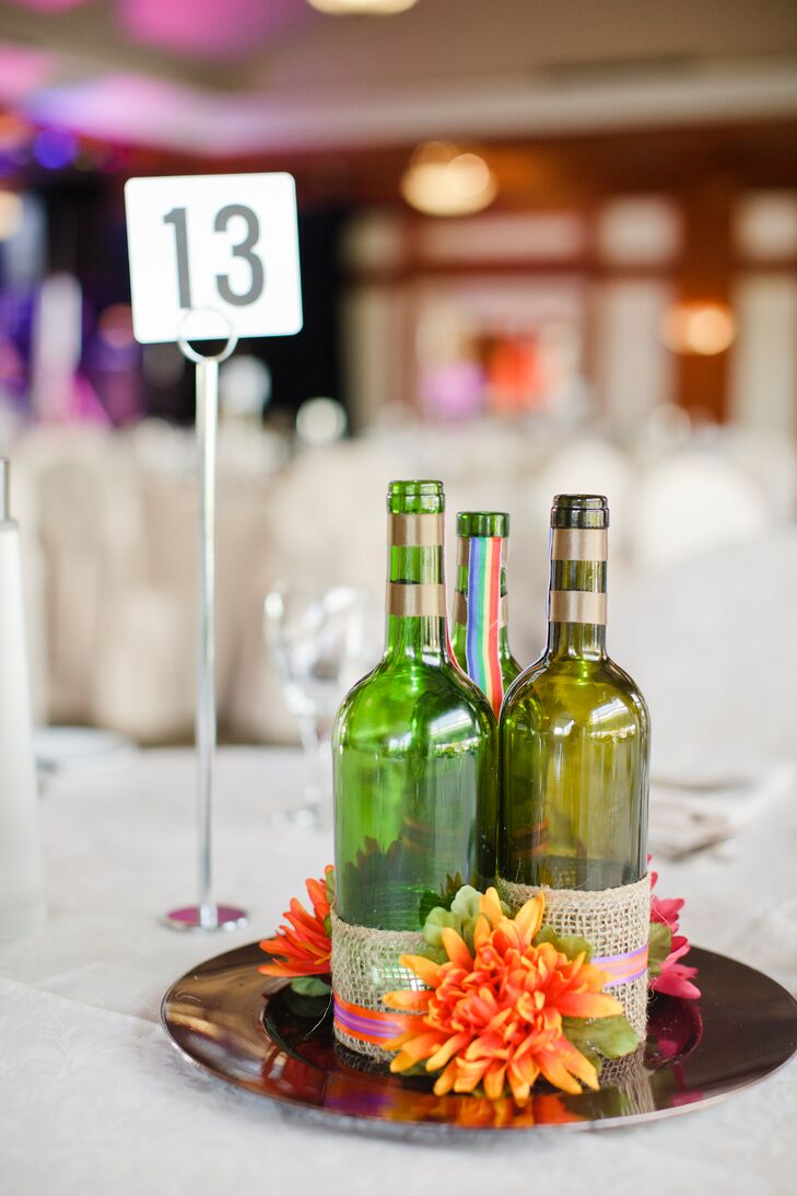 Empty wine bottles and orange flowers added a bright, whimsical touch to the centerpiece decor.