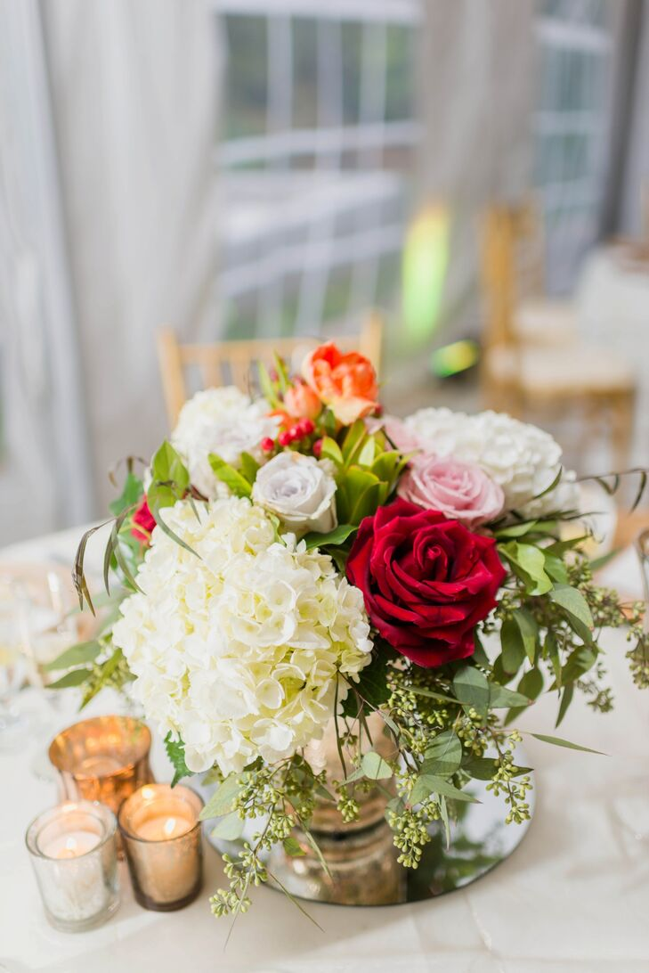 Romantic arrangements of white hydrangeas and red, white and pink roses stood in the center of the round tables at the reception.