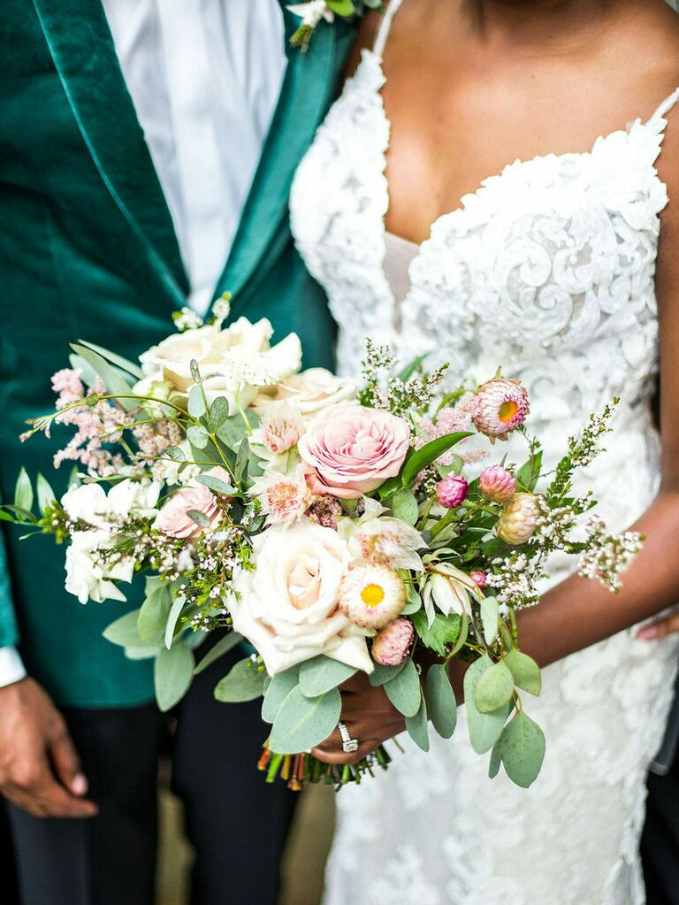 Bride and groom with wedding bouquet of pink and ivory roses