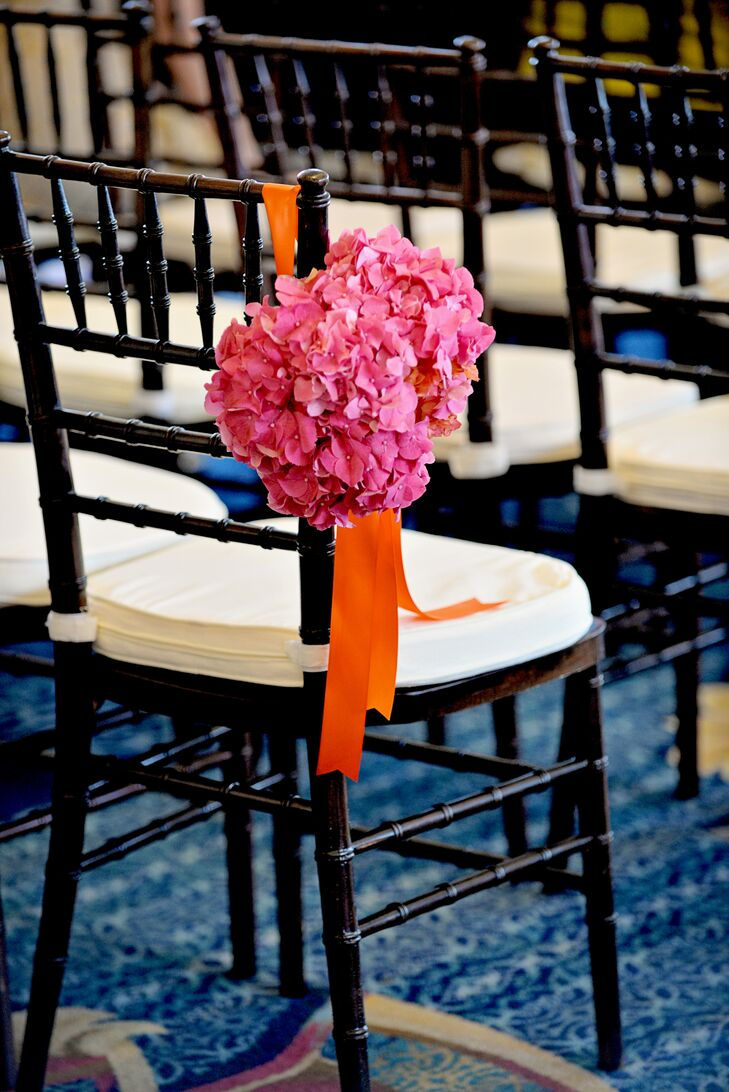 With a spectacular waterfront venue right on Boston Harbor, Ashley and Matthew decided to let the views take center stage and kept the ceremony decor simple. Black chiavari chairs lined the ceremony aisle, with alternating rows boasting bright bunches of pink hydrangeas accented with vibrant orange bows.
