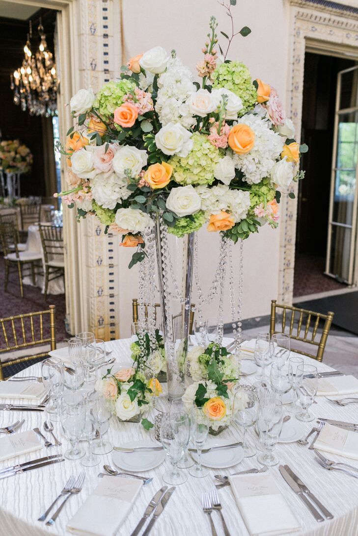 The centerpieces were one of the couple's favorite details and an integral element in bringing their garden-inspired vision to life. Displayed atop tall fluted glass vases, each arrangement featured hydrangeas, roses, stock and eucalyptus in cheerful shades of peach, coral, pink green and white. Florist Diana Gould draped crystal strands around the vessel's base to add an element of luxury to the centerpieces' overall look.