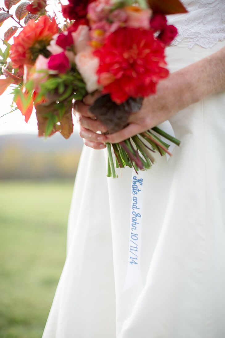 """A white ribbon stitched with the couples' names and wedding date finished Katie's bridal bouquet, serving double duty as a wrap and Katie's """"something blue."""" John held an identical ribbon in his suit pocket throughout the big day."""