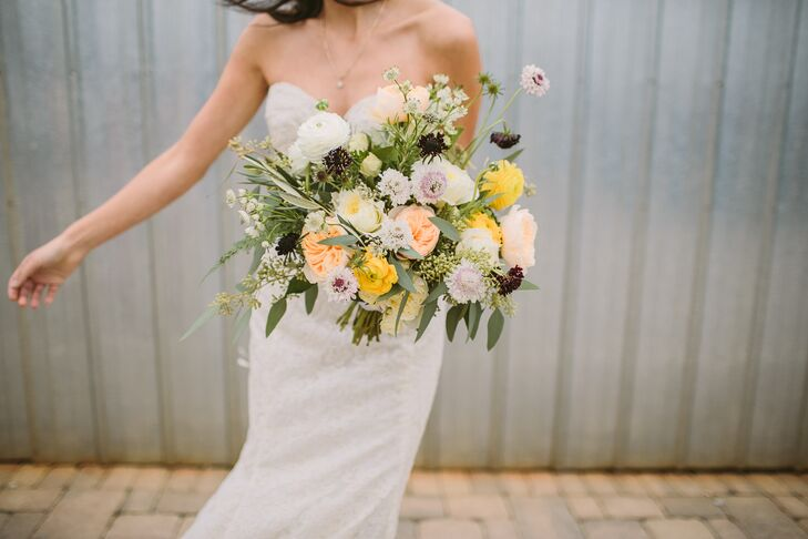 Foxglove Studio took the lead on all of the wedding's florals, using olive leaves, dahlias, scabiosas, roses, ranunculuses, lavender, cosmos, ferns and astrantia and wildflowers to fill Stephanie's breathtaking bouquet.