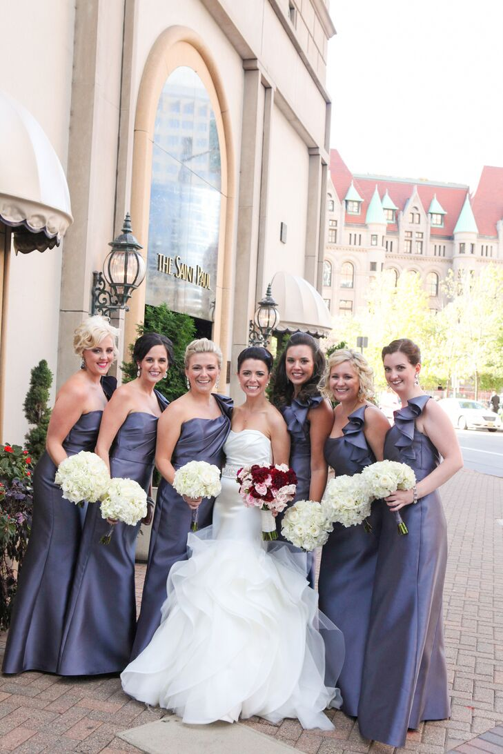 After a long search for the perfect dress for her bridesmaids, Lindsay finally came across an elegant Alvina Valenta gown that fit the wedding's formal, romantic style and complemented her own dress. The fit-and-flare silhouette and ruffled one-shoulder neckline was flattering on all of the girls, making it an obvious choice. They paired the look with their choice of jewelry from Rent the Runway and polished updos.