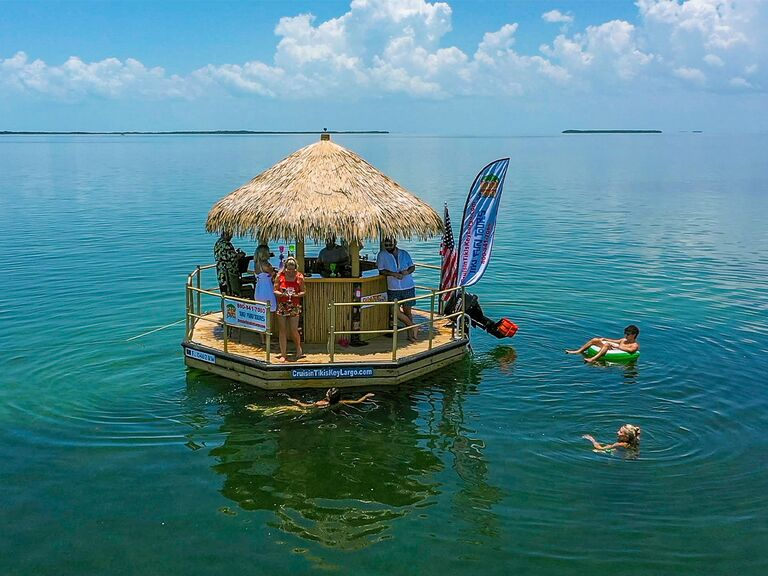 People riding on a tiki hut boat with other people in the water on tubes