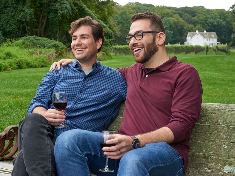 Newlywed couple Jason and Franklin sitting on a bench on a lawn with glasses of wine