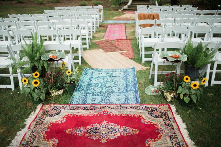 Ceremony with rug aisle runners and sunflower decorations
