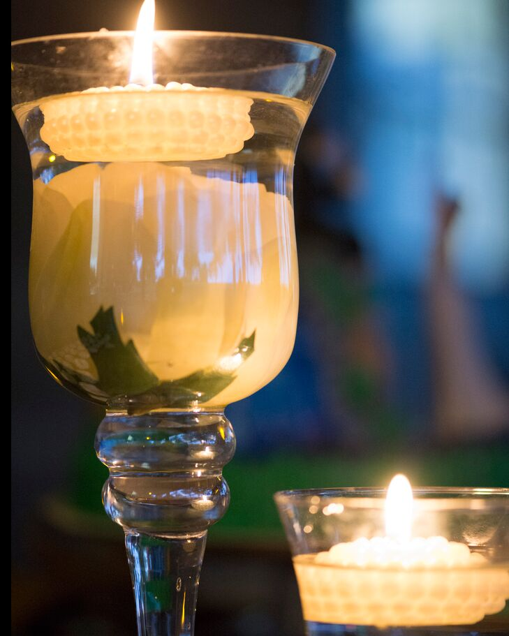 The centerpieces were goblets filled with white roses and topped with floating candles for shabby chic look.