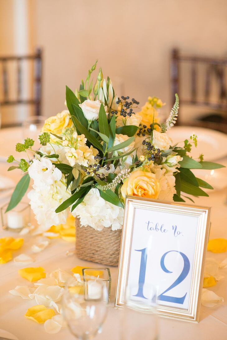 Each table highlighted the couple's nautical style with an understated design. Rope wrapped around every breakaway vase. Greenery, blueberries, yellow delphiniums, white lisianthus, white veronica and yellow roses overflowed from the accents. Surrounding yellow and white flower petals made it look even more natural.