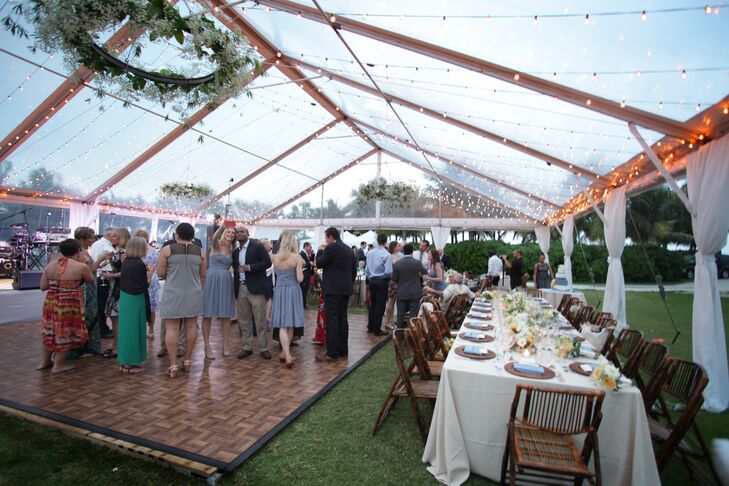 The couple decorated their reception with round and family-style tables, rattan chargers, neutral linens, French blue napkins, floral centerpieces, bamboo chairs and grapevine wood accents.